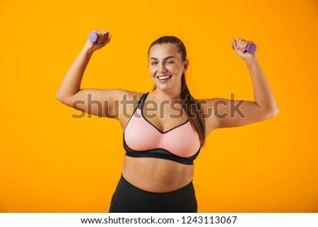 Portrait of young big sportswoman in sportive bra lifting dumbbe Stock photo © deandrobot