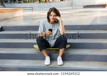 Handsome happy oung skater guy sit in the park listening music with earphones using phone. Stock photo © deandrobot