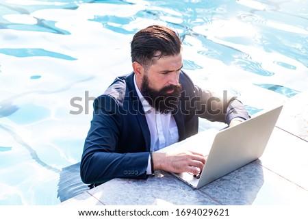 Young freelancer working on vacation next to the swimming pool Stock photo © galitskaya