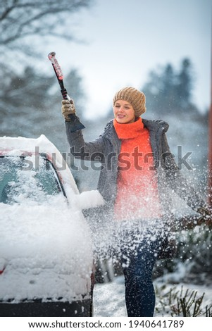 pretty young woman cleaning her car from snow after heavy snowstorm stock photo © lightpoet