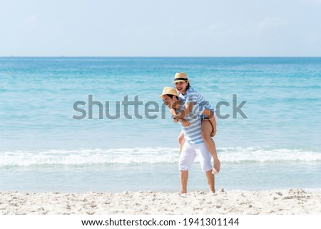 A Man and woman in love enjoying together near sea, running by the beach, laughing, kissing Stock photo © ElenaBatkova