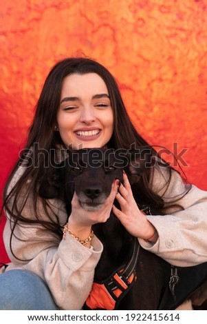 Stock photo: Young woman with her black dog  outdoor, in a park playing frisbee