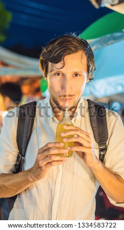 Man drinking sugar cane juice on the Asian market VERTICAL FORMAT for Instagram mobile story or stor Stock photo © galitskaya