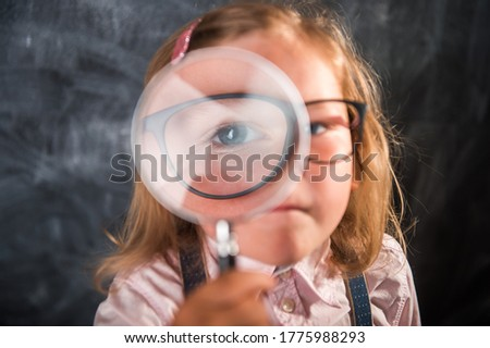 Boy and girl are looking in a magnifying glass against the background of the garden. Home schooling stock photo © galitskaya