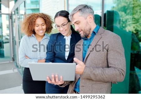 Group of young intercultural managers with laptop getting ready for conference Stock photo © pressmaster
