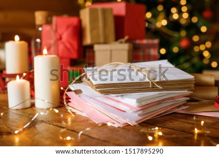 Stack of letters for Santa, three burning candles and group of packed gifts Stock photo © pressmaster