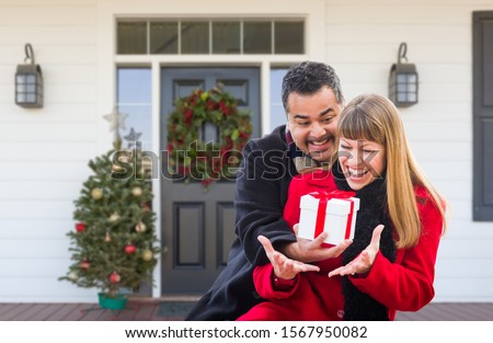 Young Mixed Race Couple Exchanging Gift On Front Porch of House  Stock photo © feverpitch