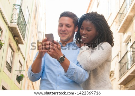 Happy young intercultural female tourist with smartphone making selfie Stock photo © pressmaster