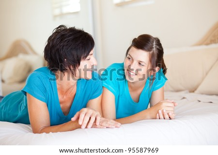 Relaxed mother and daughter in lie in bed with white bedclothes, enjoy comfort at home in spacious b Stock photo © vkstudio