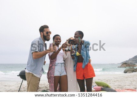 Front view of multi ethnic group of friends reviving photo on mobile phone at beach while drinking b Stock photo © wavebreak_media