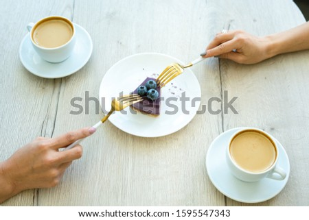 Hands of girls with forks taking piece of tasty blueberry cheesecake on plate Stock photo © pressmaster