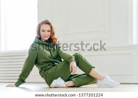 Sideways shot of satisfied redhead woman has makeup, wears tracksuit, white spotshoes, rests on floo Stock photo © vkstudio