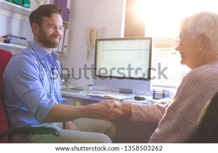 Side view of Caucasian male doctor interacting and shaking hand with female senior patient in clinic Stock photo © wavebreak_media