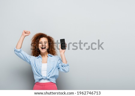 Image of cheerful woman rejoicing while holding blank thought bu Stock photo © deandrobot