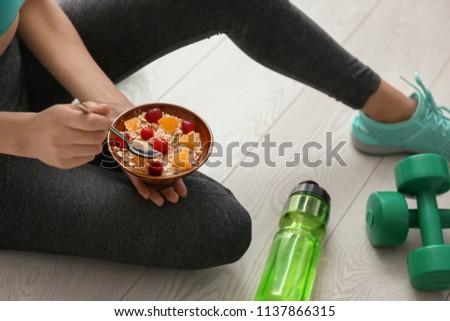 Obraz młoda kobieta odzież sportowa posiedzenia piętrze treningu Zdjęcia stock © deandrobot