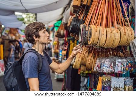 Man at a market in Ubud, Bali. Typical souvenir shop selling souvenirs and handicrafts of Bali at th Stock photo © galitskaya
