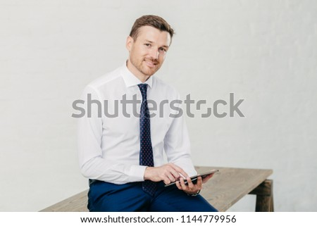 Happy male CEO makes online transaction on modern tablet computer, dressed in formal wear, poses on  Stock photo © vkstudio