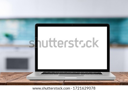 Laptop with blank screen against blurred kitchen interior background. Stock photo © artjazz