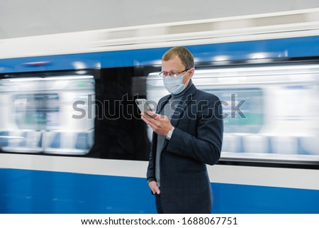 Young man manager uses cellphone, prevents spreading of Coronavirus, poses against subway train, pos Stock photo © vkstudio