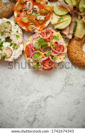 Homemade Bagel sandwiches with different toppings, salmon, cottage cheese, hummus, ham, radish Stock photo © dash