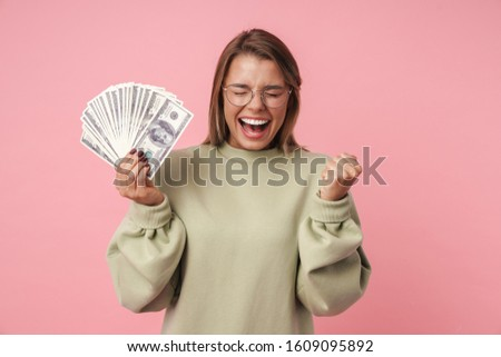 Portrait of nice excited woman holding banknotes while screaming Stock photo © deandrobot