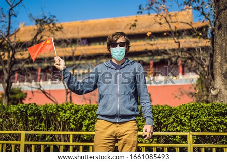 Enjoying vacation in China. Young man in medical mask with national chinese flag in Forbidden City.  Stock photo © galitskaya