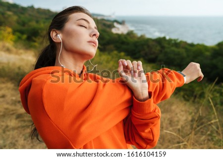 Photo of athletic woman stretching her arms and using earphones Stock photo © deandrobot