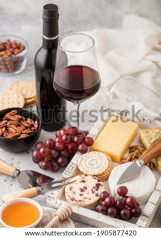 Selection of various cheese in wooden box with grapes and nuts on wooden table background. Blue Stil Stock photo © DenisMArt