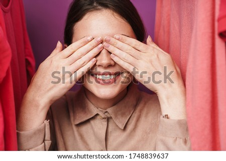 Photo of woman covering her eyes while standing at clothes rack Stock photo © deandrobot
