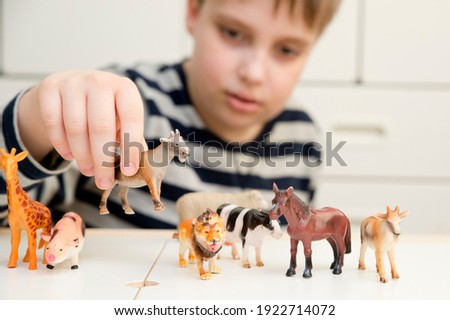 Young boy playing with a selection of toy figurines and animals Stock photo © photography33