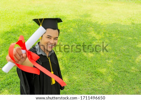A smiling graduate with his degree in hand as he looks at the camera  Stock photo © wavebreak_media