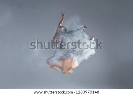 Young beautiful dancer in beige dress dancing on gray background Stock photo © master1305