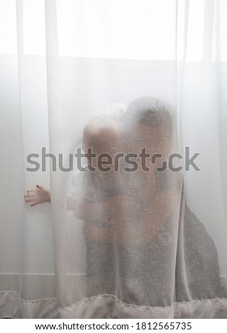 Happy playful young woman hiding behind white curtains and smiling Stock photo © deandrobot