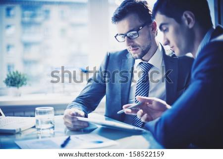 two young businessmen discussing business plan and using tablet stock photo © deandrobot