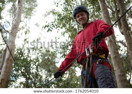 Young hiker man wearing safety helmet holding zip line in the forest during daytime Stock photo © wavebreak_media