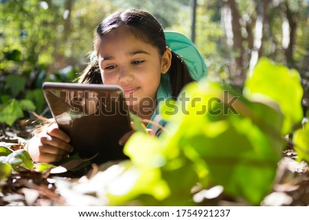 Little girl with backpack lying on ground using her tablet on a sunny day in the forest Stock photo © wavebreak_media