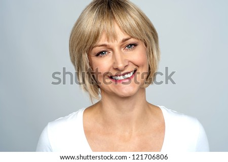 Portrait of a smiling middle aged caucasian woman against dark background Stock photo © lightpoet