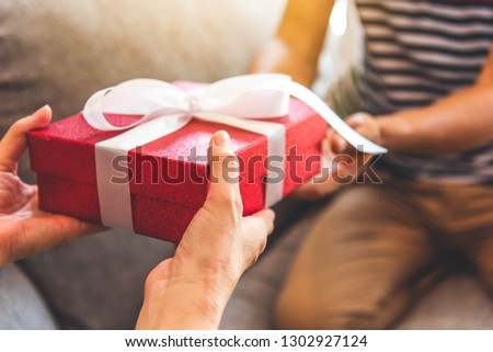happy loving couple holding present gift boxes for each other stock photo © deandrobot