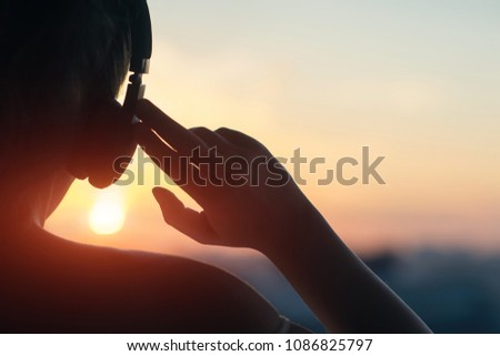 Sports woman outdoors on the beach listening music with earphones make stretching exercises. Stock photo © deandrobot