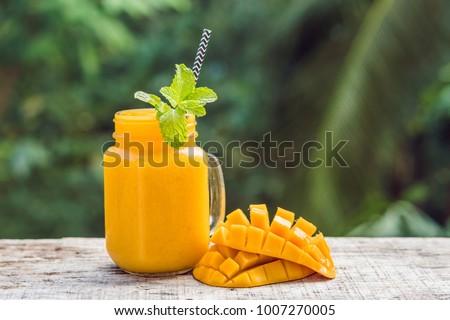 Stock photo: Mango smoothie in a glass Mason jar and mango on a green background. Mango shake. Tropical fruit con