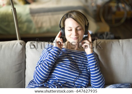 woman sitting on the couch take some good time with music headphone, Stock photo © Lopolo