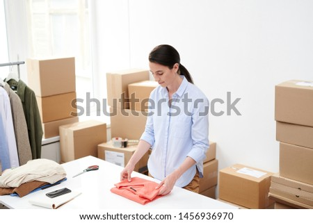 Young female online shop worker folding red pullover for packing Stock photo © pressmaster