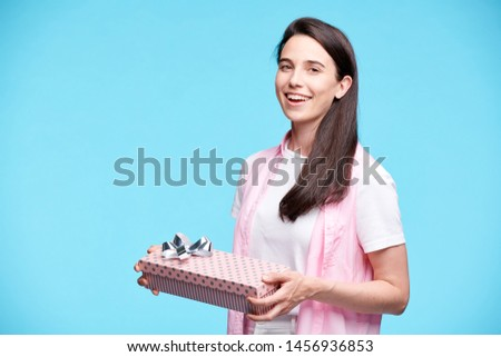 Young excited brunette woman in casualwear holding packed giftbox Stock photo © pressmaster