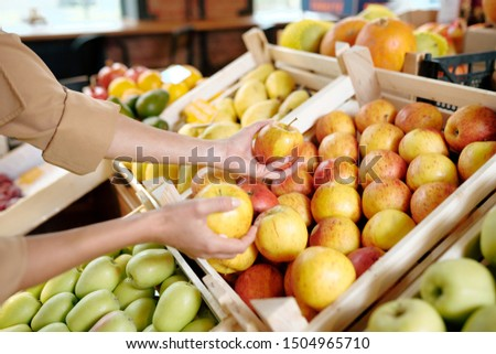 Hands of young woman taking two ripe yellow apples from wooden box Stock photo © pressmaster