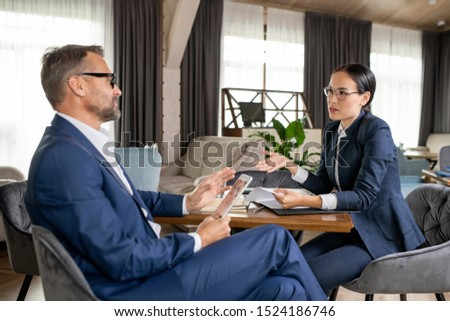 Young confident Asian businesswoman explaining her opinion to colleague Stock photo © pressmaster