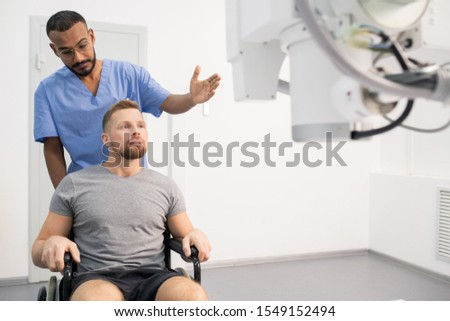 Young doctor in uniform showing sick man on wheelchair new medical equipment Stock photo © pressmaster