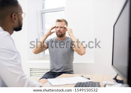Young bearded man touching his head while complaining on permanent headache Stock photo © pressmaster