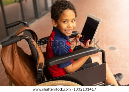 Side view of happy cute mixed-race disabled schoolboy with digital tablet looking at camera in corri Stock photo © wavebreak_media