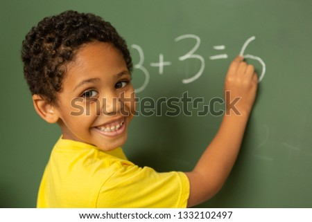 Rear view of focused mixed-race schoolboy doing math on greenboard in a classroom at elementary scho Stock photo © wavebreak_media