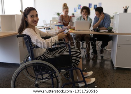 Stock photo: Side view of pretty disabled mixed-race female executive discussing with coworker over digital table